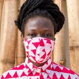 Model wearing a face mask printed with repeating rows of vibrant pink triangles, and a matching collared shirt.