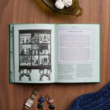 A book on a wooden tabletop surrounded by accessories, open to an interior spread featuring an illustration of a dollhouse on one side and text on the left.