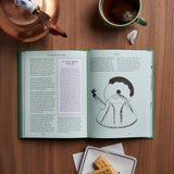 A book on a wooden tabletop surrounded by a teapot, mug, and cookies, open to an interior spread featuring an illustration of a kettle on one side and text on the left.