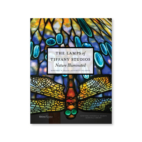 "A book cover shows a close up detail of a stained glass Tiffany lampshade.  The title, ""THE LAMPS of TIFFANY STUDIOS – Nature Illuminated"" is printed in black text inside a white semi-translucent box centered on the cover.  Dominating the lower half of the book is a stained glass butterfly hanging upside down with its head down toward  the bottom of the book. Two round green eyes face forward and appear to glow as they sit atop a red body. The wings illuminate showing a mosaic of more intricate fragments."