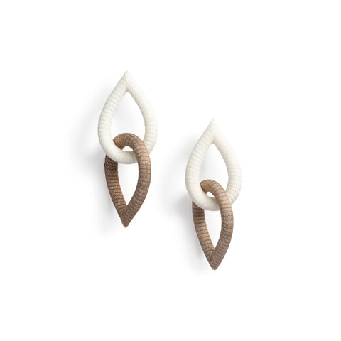The Loop Double Earrings, each made of two textured interlocking teardrops, one white and one camel-colored.