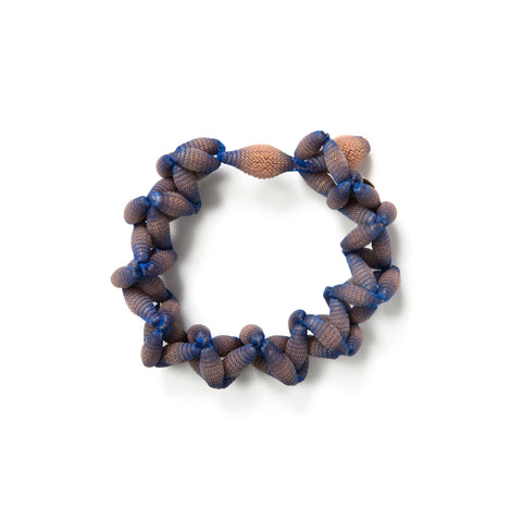 Several desaturated orange silicone beads incased in blue lace form a bracelet with a loop closure