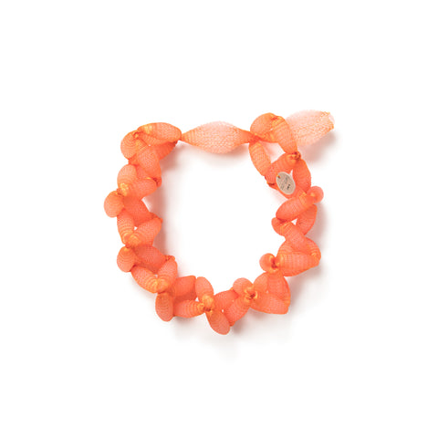 Several white/ translucent silicone beads incased in a vibrant orange lace form a choker with a loop closure