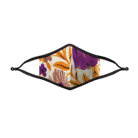A floral print cloth face masks with black trim and adjustable ear loops. Colors included in the floral print are purple, yellow, blush, and black..
