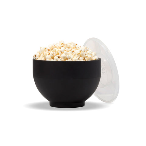 Matte black bowl full of popcorn, clear lid with air-holes leans against the side.