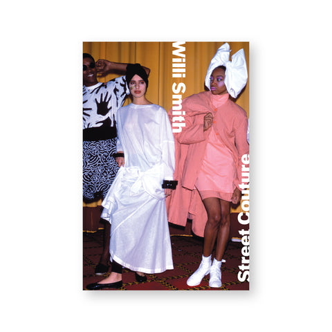 "Rectangular book cover featuring a photograph of three fashion models. The two on the right wear oversized garments and headpieces with dramatic makeup while the model on the left wears graphic black-and-white fabric and sunglasses. Overlaid in white is the text ""Willi Smith: Street Couture."""