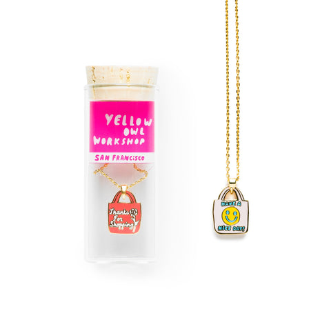 "Small glass vial with cork top containing the enamel Have A Nice Day Pendant on a gold chain: a coral shopping bag that says ""Thanks for Shopping"" in white script with a white illustration of a rose. There is another Have A Nice Day Pendant next to the vial displaying the reverse side: a pale shopping bag that says ""Have a Nice Day"" in blue with a yellow smiley face."