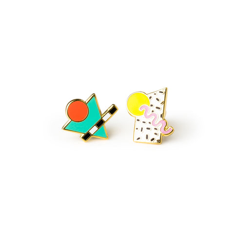 The enamel Memphis Style Earrings, magnified. Each post earring is different: one is a teal triangle with a red circle and a black and white striped bar, the other is a black and white speckled rectangle with a yellow circle and a pink squiggle.