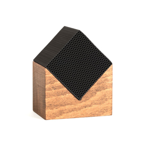 A small black cube resting on a wooden stand. The cube has tiny holes through it that resemble a honeycomb.