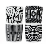 Four coffee mugs, stacked in pairs. All are black and white with varying geometric and optic patterns.
