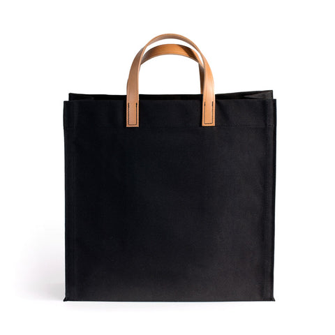 Black square shaped canvas bag with medium brown leather handles