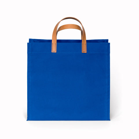 Cobalt blue square shaped canvas bag with medium brown leather handles