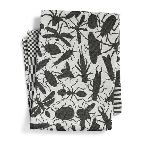 Off white textile with a black pattern of insect silhouettes, folded. Pattern is bordered by a checkered pattern along the edges.