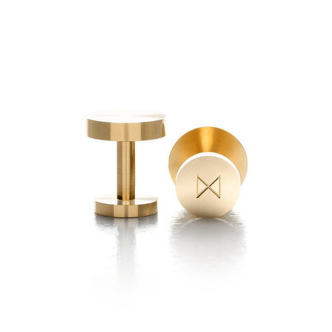 A pair of solid brass cufflinks. The brand's logo is etched into th base of the cufflink.