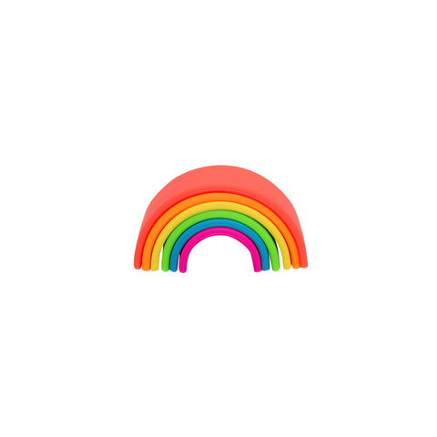 Front view, slightly above, of the dena Neon Rainbow Toy. The toy is made up of six, matte neon, upside-down U shapes, each larger than the next, stacked on top of each other to form a rainbow. The neon colors are coral red, orange, yellow, green, blue, magenta.
