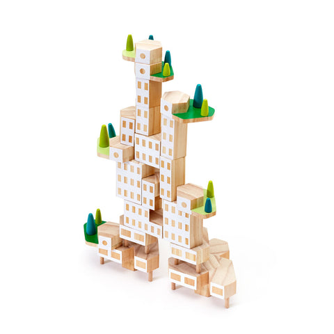 On a white background an angled image of an assembled unfinished wood building block set. It is put together to form one building but with various sized hexagonal shaped blocks forming two asymmetric towers. Six elevated platforms that look like mini terraces are staggered throughout the structure and have green surfaces with trees.