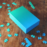 Green to blue Gradient Puzzle on wood table with scattered puzzle pieces around it.