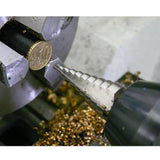 A coin being held in a vice while a drill bit shaves it down. Gold shavings form a pile underneath.