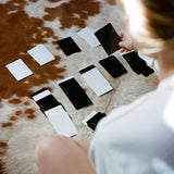 On top of cow hide rug, a person plays solitaire with a mix of black and white Minim playing cards.