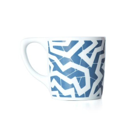 White coffee mug with a blue printed zig zag pattern.