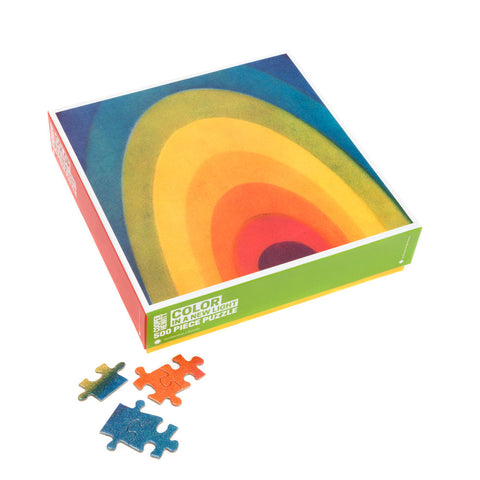 Colorful box showing a rainbow of curved bands on top with red and green sides and a yellow base. Five blue and orange puzzle pieces sown outside box some interlocked