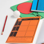 An image of the three table tennis notebooks laid out and overlapping each other. A ping pong ball and pencil are included in the grouping.