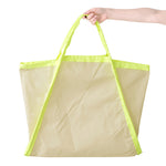 Expanded view of a large triangle-shaped bag with natural colored body and neon yellow trim. Expanded sides turn the bag into a large square.