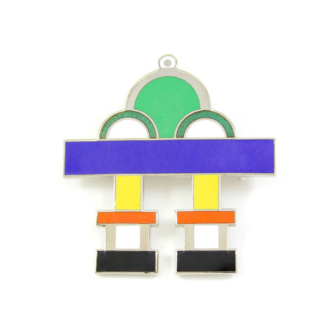 A brooch is designed from an abstract combination of geometric forms using green, white, blue, yellow, orange, and black colors.