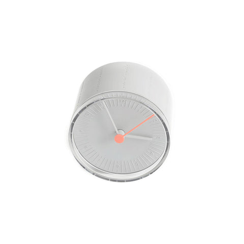 A round gray desk clock with matching gray hour and minute hands. The second hand is featured in orange.