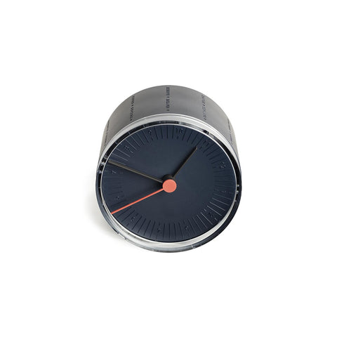 A small round desk clock in navy blue. The hands on the clock are gray with orange hand indicating the seconds.