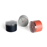Three round desk clocks in navy, gray, and red.