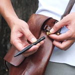 Lifestyle image of hands holding the Black Brassing Portable Ball Point Pen, detaching it from the shackle which is attached to a loop on a leather messenger bag.