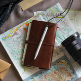 Lifestyle image of the white Brassing Portable Ball Point Pen, lying on a leather notebook on top of a map, surrounded by a camera lens and other papers.