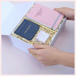 Hands holding an open gift box filled with pink notepad, navy trinket, gold pen and lip balm