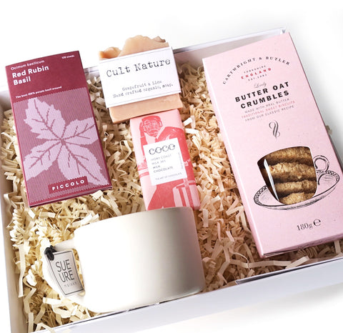 Pink gift box with basil seeds, ceramic mug, biscuits, chocolates and organic soap