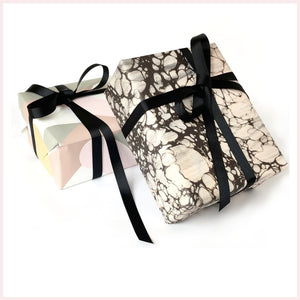 Luxury wrapping paper with black ribbon on two gift boxes