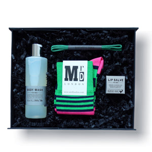 gift box for men with body wash, lip balm, green shoe laces and green and pink striped socks