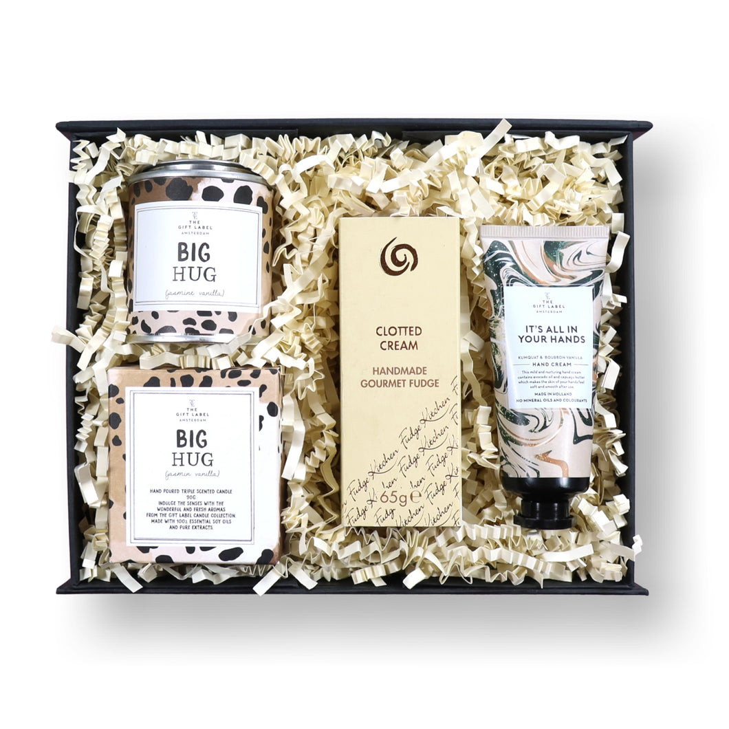 Matt black gift box filled with a big hug scented candle, clotted cream trio of fudge and hand cream.