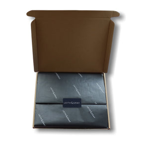 Letterbox gift packaging with black Leith & Gray tissue paper and a black Leith & Gray sticker.