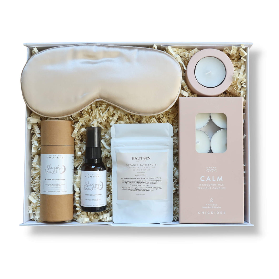 Gift box filled with products to aid sleep including eye masks, face cream, bath salts, pillow spray and tea lights.