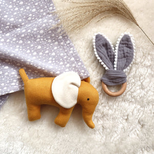Flat lay of muslin, teether and soft toy elephant