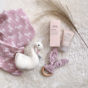 New baby gift flat lay showing muslin, teether, swan rattle and baby balm