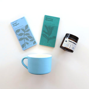 Blue mug, seed packets, and a scented candle