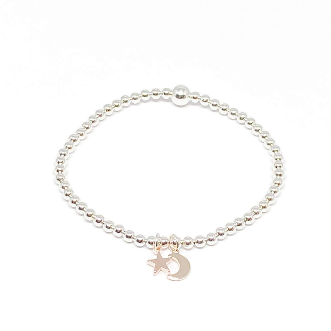 Elasticated silver beaded bracelet with a rose gold moon and star charm