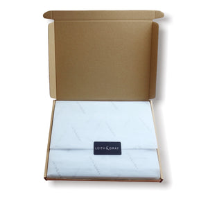 Letterbox packaging box with white Leith & Gray tissue paper and a Leith & Gray sticker