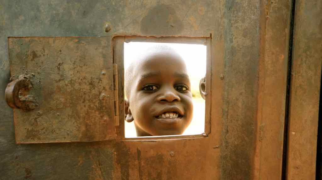 African boy smiling through a metal door. Cute. Taken by stone unknown in 2012.
