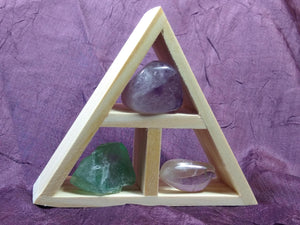 This wooden handcrafted triangle is made of fir and holds three stones and crystals intuitively selected to help you in your intentions for meditation.
