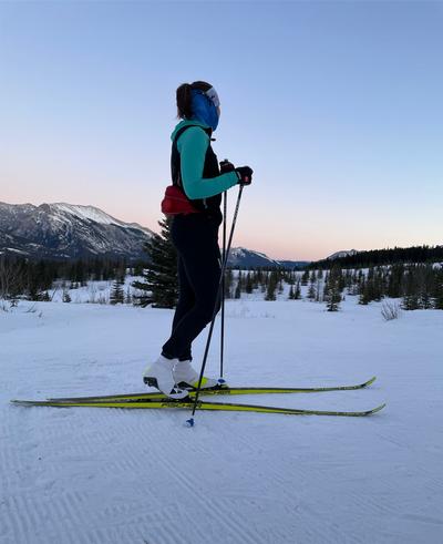 Woman Nordic Skiing at sunset in Mountains