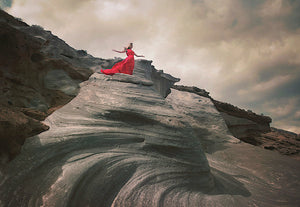 Beautiful woman in the red dress standing on the pedestal rock