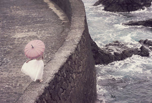 Woman in white dress and with pink umbrella walking on the edge of a pier